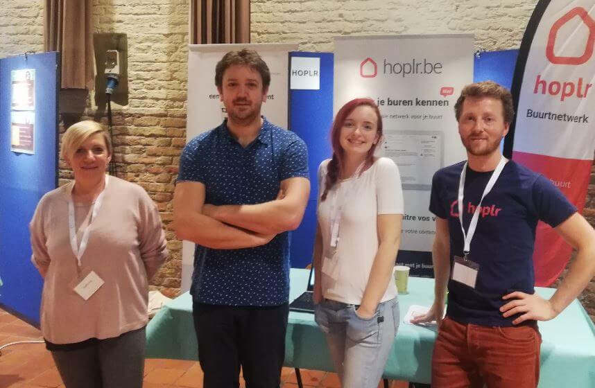 two Hoplr team members and two ambassadors pose together at a trade fair for neighbours in Bruges