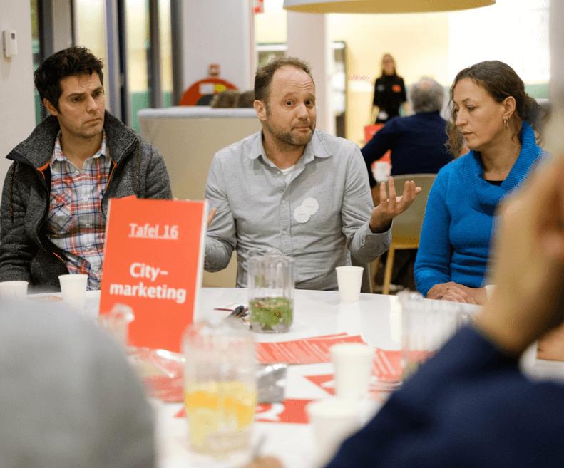 burgers zitten rond de tafel en bespreken citymarketing