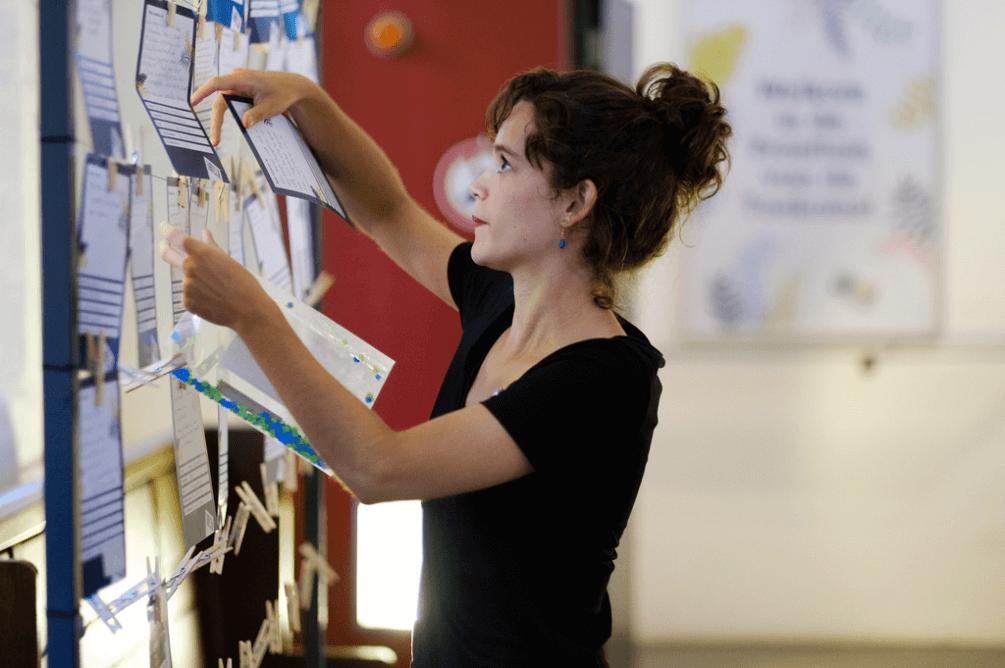 vrouw hangt voorstellen burgerparticipatie op een bord