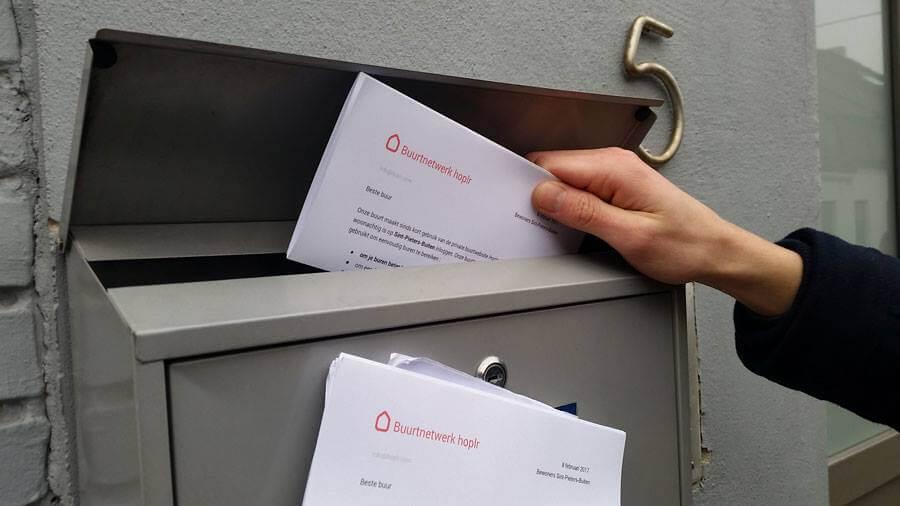 quelqu'un met une lettre d'invitation pour Hoplr dans une boîte aux lettres