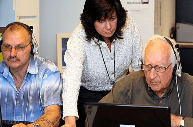 vrouw helpt ouderen met gebruik computer