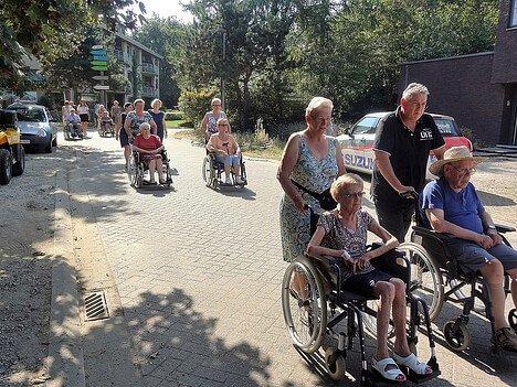 les voisins et la famille sortent ensemble, beaucoup d'entre eux assis dans un fauteuil roulant