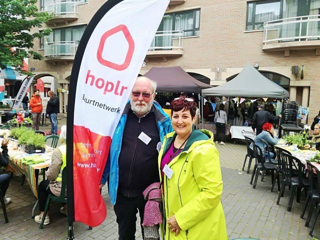 Twee buurttrekkers vertegenwoordigen Hoplr op evenement voor burgers, staan naast Hoplr-banner